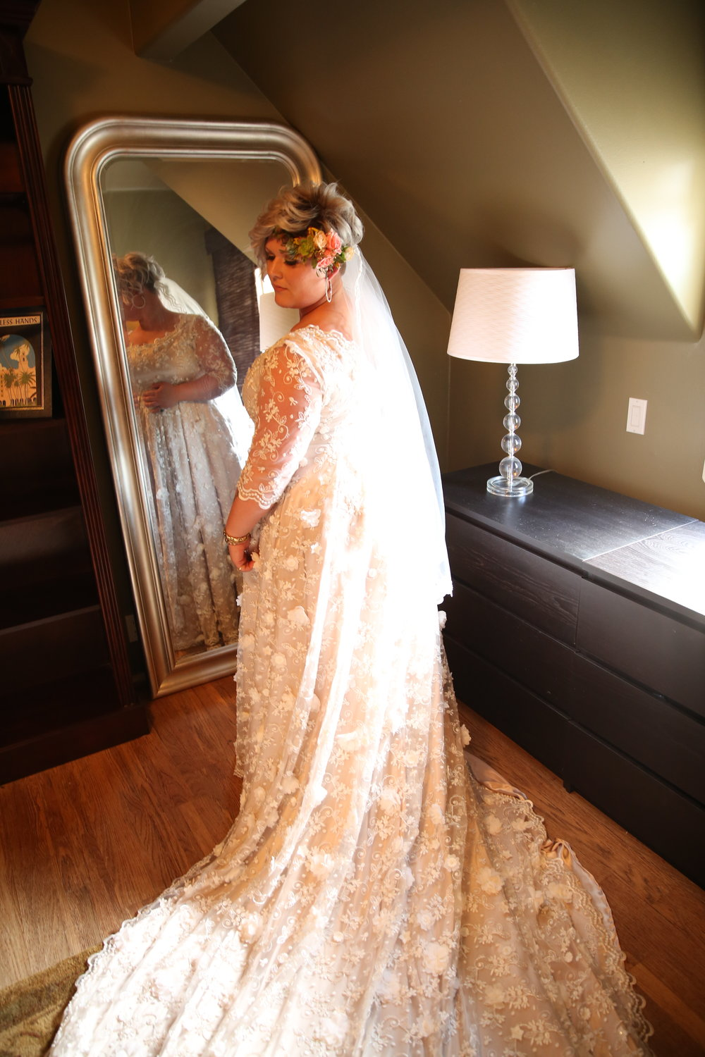 Bride in a wedding dress with a train, looking over her shoulder standing in front of a mirror. She is ready to walk down the aisle.