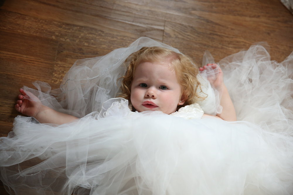 Cute red haired flower girl in a cream tulle dress. Waiting to walk down the aisle.