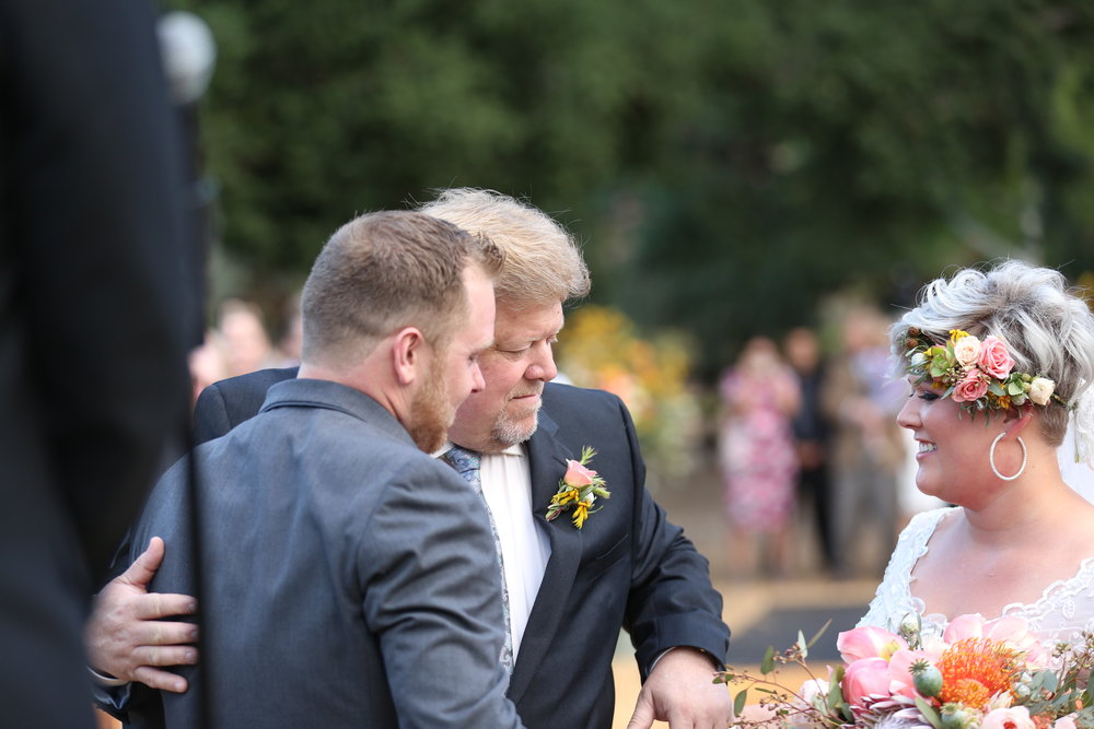 The father of the bride as he gives his daughter bride away at her wedding ceremony to a handsome groom who sees her for the first time.