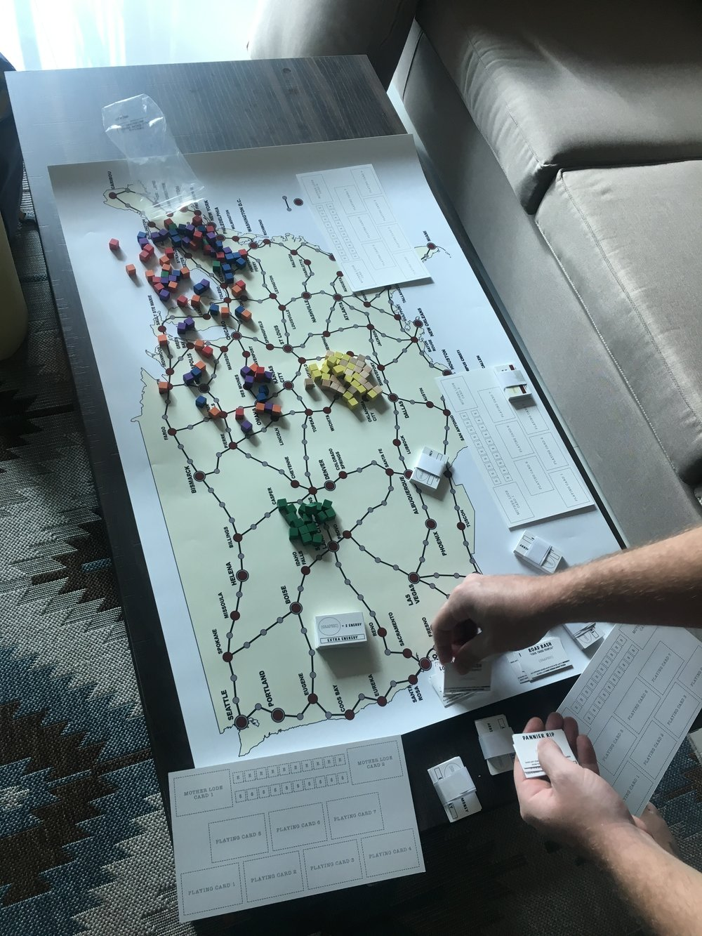 The first color print of the board game. Still a prototype, but we were still playing through all the bugs. You can also see the second prototype of the panniers and playing cards. The cubes on the board we pulled from another game and represent the essential pieces of the game.