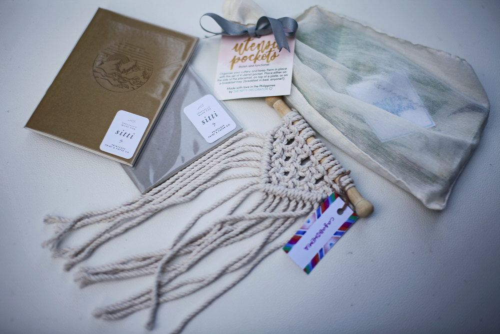 Specially-designed journals from Print Cafe, a cute macrame wall hanging from Casa Bohemia, and unique utensil pockets from The Nifty Decorator.