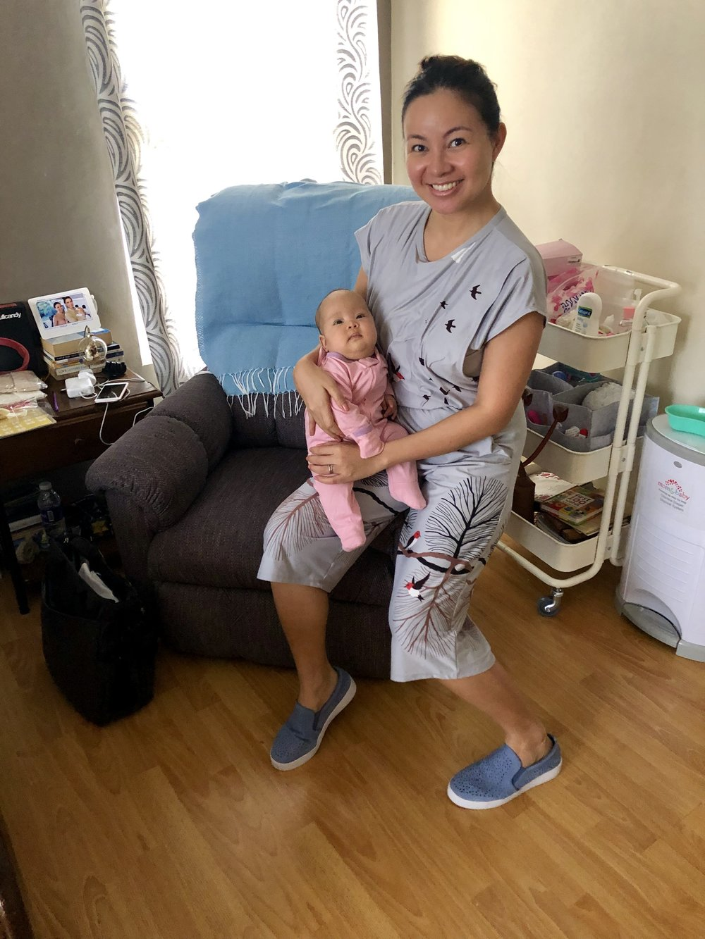 Posing with Lilibubs in my nursing corner - our recliner with all my essentials in a trolley on the side. Our trusted diaper pail is captured here too :) this picture was taken on February 1st; Lilibubs was almost thirteen weeks old then. Her zipper footie that we like so much is from @babysoyph . My nursing romper is from @nazzycollection . The hubs complimented me on them :)