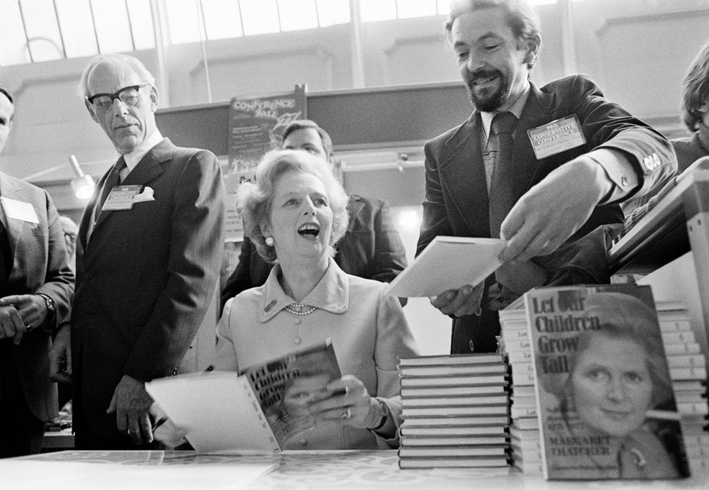 GB.Brighton. The Conservative Party Conference. Margaret THATCHER signing copies of her book while her husband Denis THATCHER looks on.