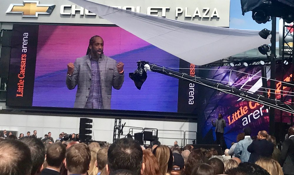 Sekou stands on stage  outside Little Caesars Arena, inspiring the audience with an inspiring Detroit Made message!