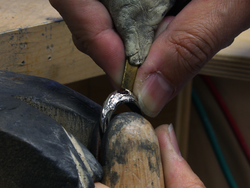 Takayas setting the garnet center stone in the axe-inspired mounting
