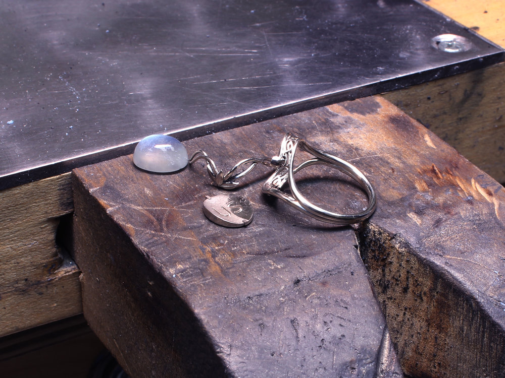 The custom Elvish Moonstone engagement ring on Takayas' workbench