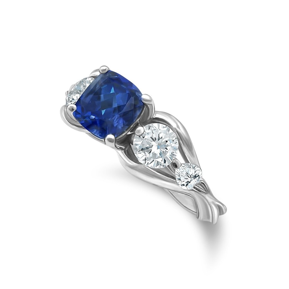 Final Fantasy XIV Carbuncle inspired engagement ring in platinum with two pear shaped accent diamonds, two 0.25 ct. side diamonds, and a 1.32 ct. cushion cut sapphire