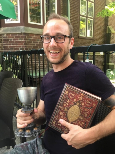 Phoenix Bar & Grill.  Ben K. D. Pearce holding the traditional Phoenix chalice and signature book after the successful completion of his Master's defense. July 21st, 2017.