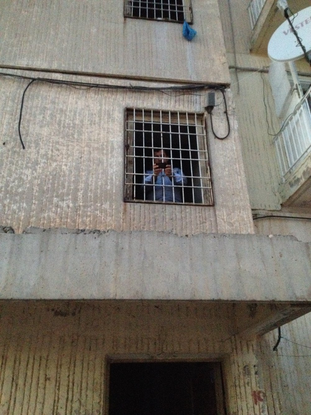 my father standing in the 2nd floor of the hallway looking out the caged windows.