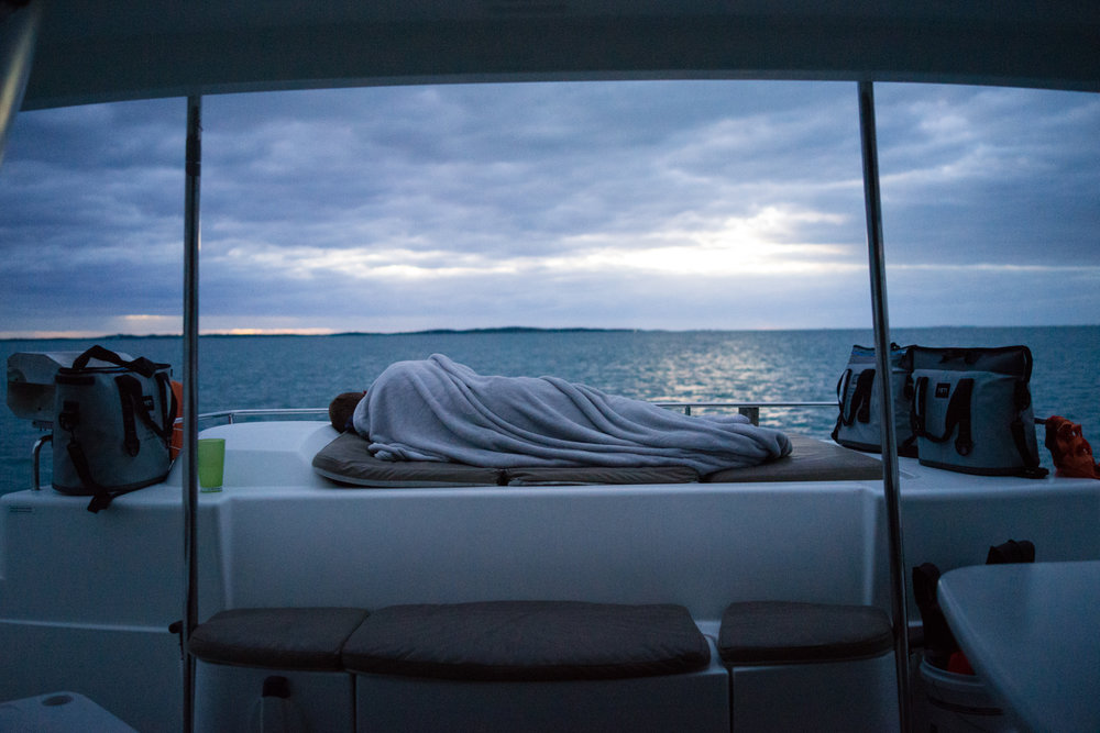 I rose early this morning to check out our skies and seas. Everyone was still asleep, including Cheffy Chris who I caught bundled up in a rare moment of repose.
