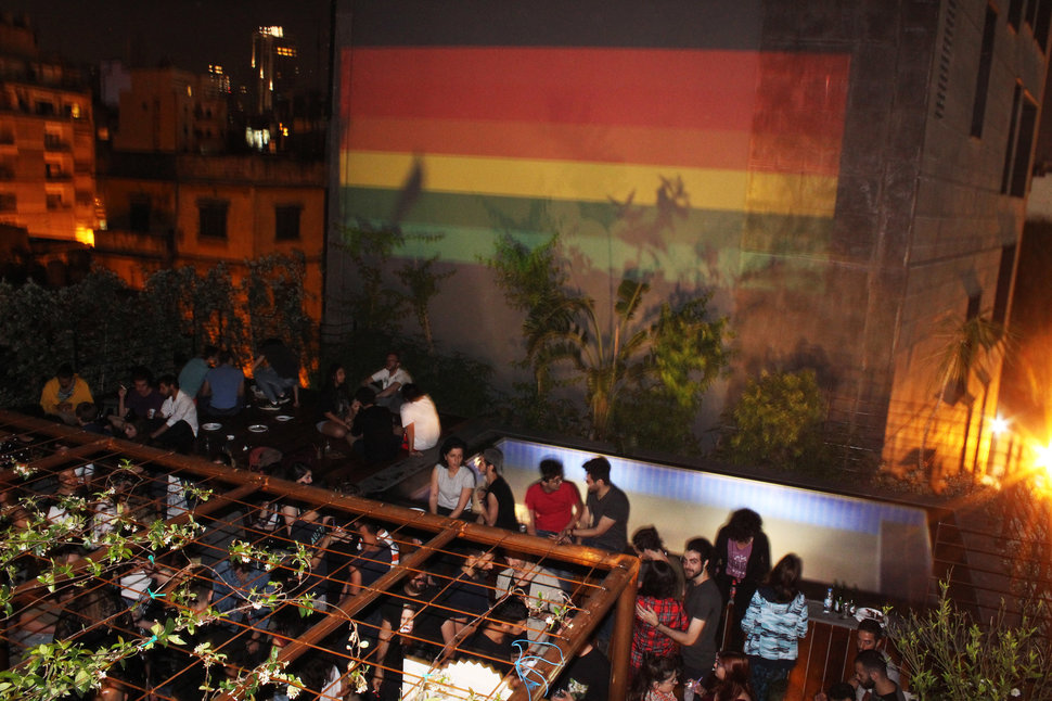 A rooftop party with a rainbow flag projected on the neighboring building during Beirut Pride 2017. (HADI DAMIEN)