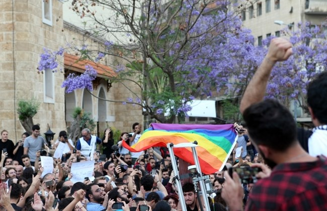 Activists carry the LGBT pride flag during a protest in Beirut, Monday, May 7, 2018. (The Daily Star/Hasan Shaaban)