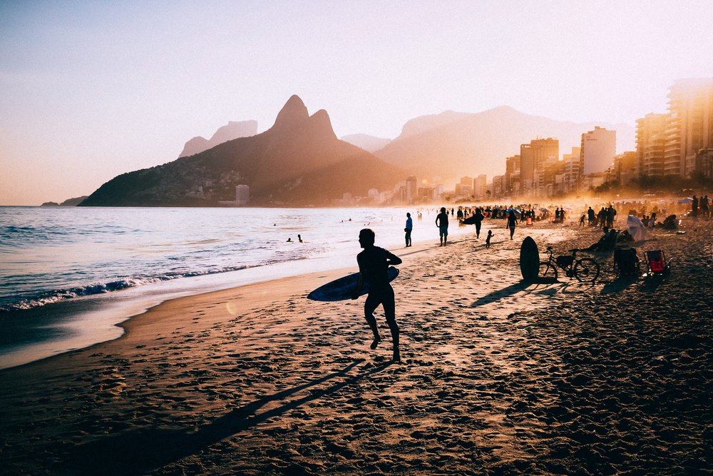 Surfers on the beach at sunset in Rio