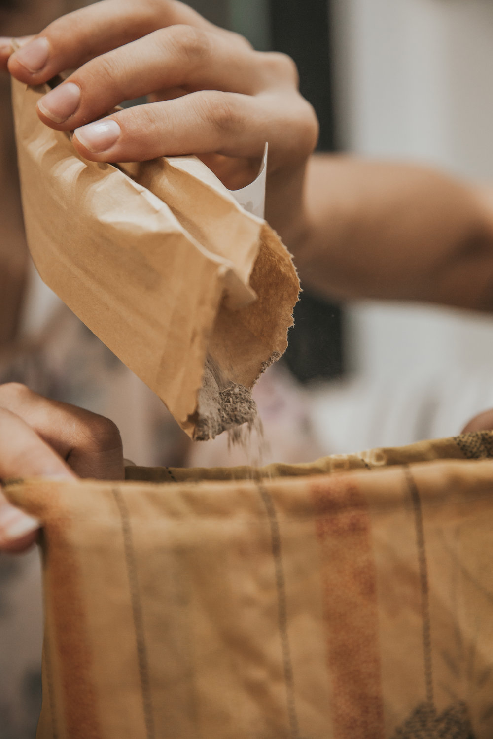 Pouring kava into a bag to strain into the bowl