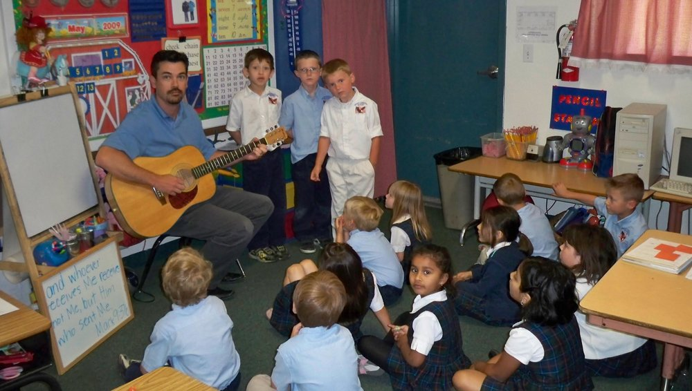 Jeff playing guitar for Kindergarten Morning Meeting