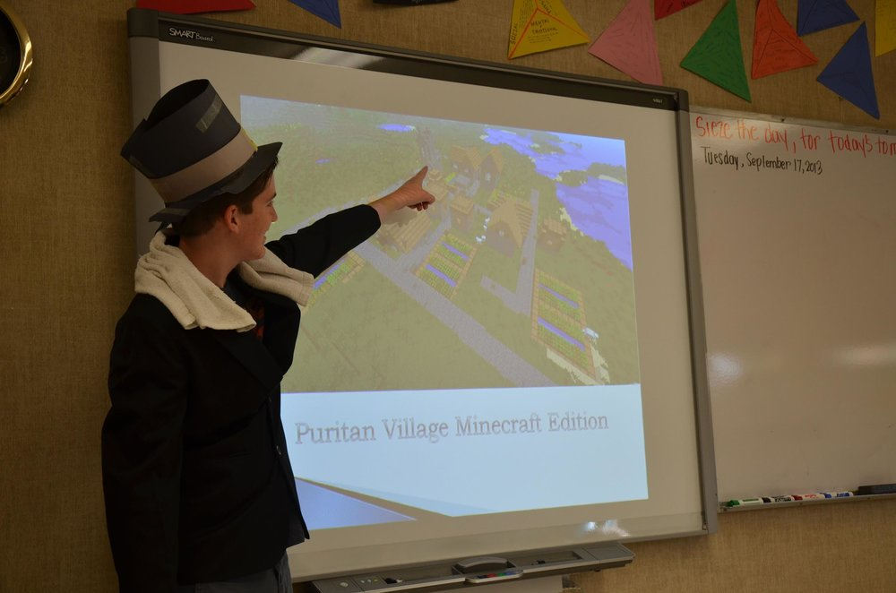 Junior American Literature student showing us his Minecraft Puritan Village in character