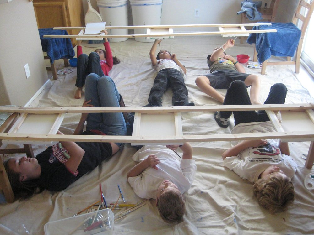 Homeschool students paint as Michelangelo painted the Sistine Chapel, on their backs looking up.