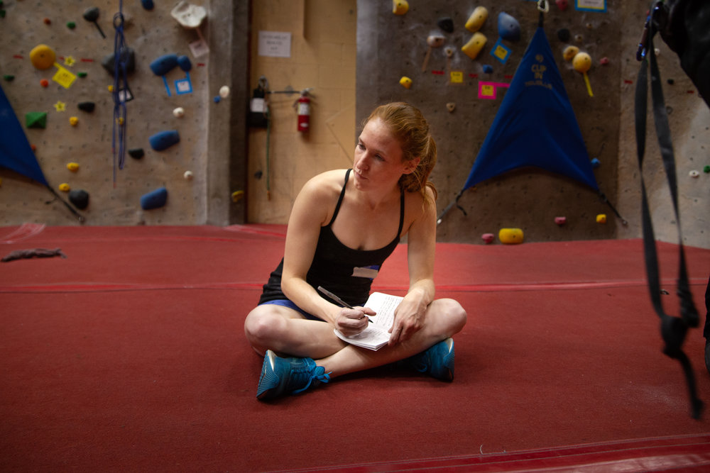 A member of Never Stop Moving logging her training workouts in her personal training log during a climbing session. Photo by  Heather DuBrall Photography