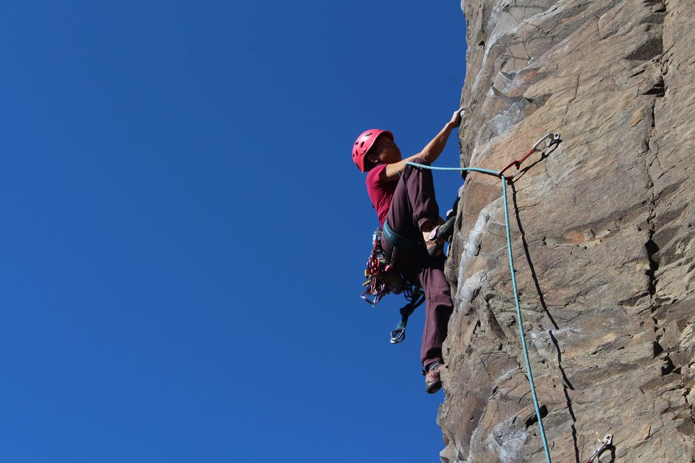 Jum, a NSM Trip Leader leading a route during a NSM outdoor climbing trip at Vantage, WA. Photo by Megan Fritz