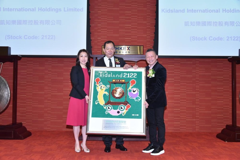 Caption: Mr. Lee Ching Yiu, Chairman and Chief Executive Officer of Kidsland International (Middle), Dr. Lo Wing Yan William, Vice-Chairman, Chief Financial Officer and Managing Director in Hong Kong (Right) presenting a souvenir (Lego plate symbolizing Kidsland) to Ms. Chan Yuen Shan Clara, Listing Committee Member.