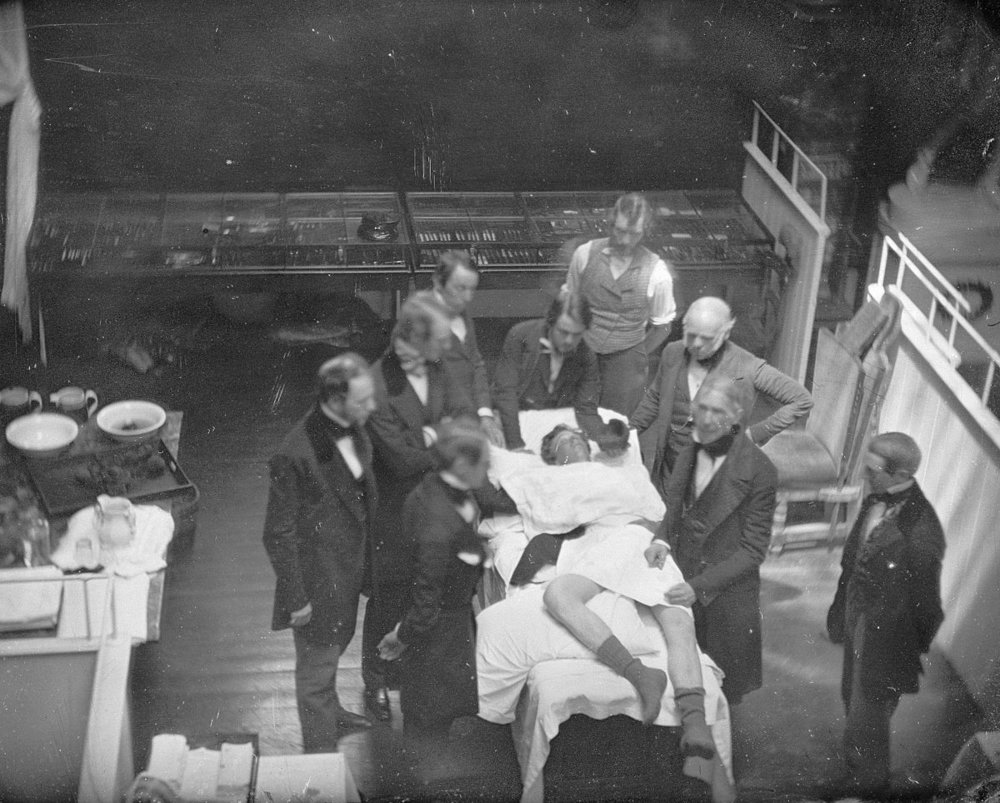 Surgeons operating in black over coats.