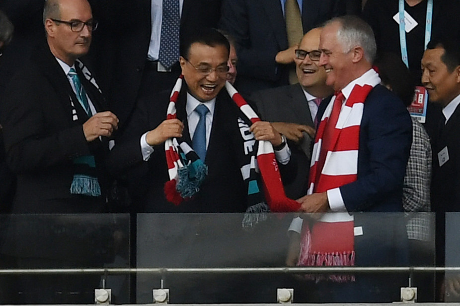 Chinese Premier Li Keqiang wears a Swans scarf at the AFL with Prime Minister Malcolm Turnbull. AAP/Dean Lewins