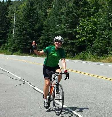 Carrie smiling as she bikes in the Lake Placid Iron Man, July 2016.