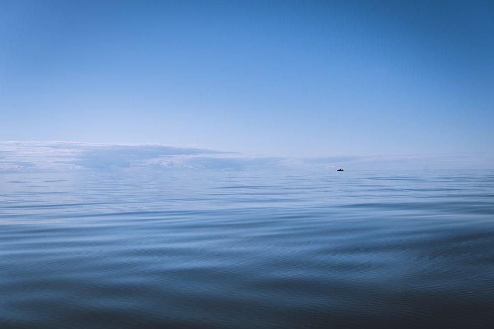Pieni kalastajavene laskee verkkoja veteen kauempana merellä.