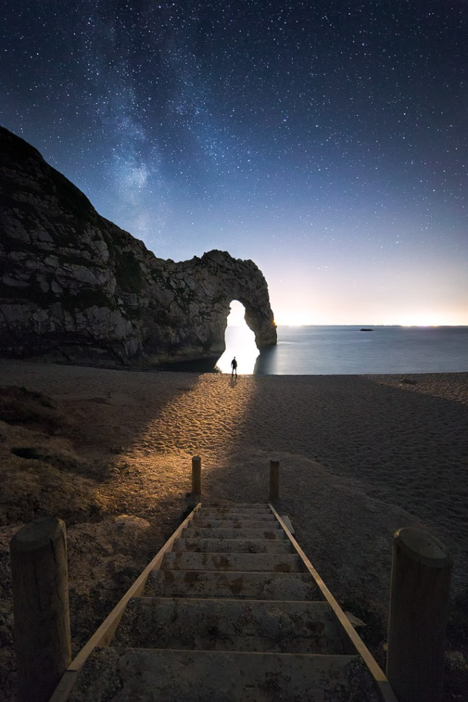 Moonlight spilling through Durdle Door as the Milky Way takes over the night sky
