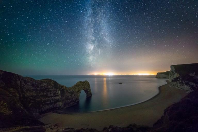 A Perseid meteor streaks along the milky way above Durdle Door