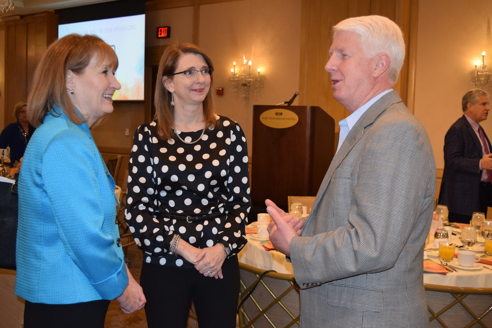 Kathleen Lynd, vice president planning and communications at Oakland Family Services, chats with Julie and Mike Richards.