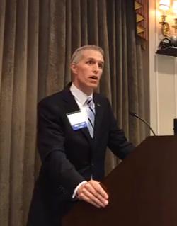 Board Chair Paul DeRoche announces the results of the 2018 Building a Brighter Future Breakfast.