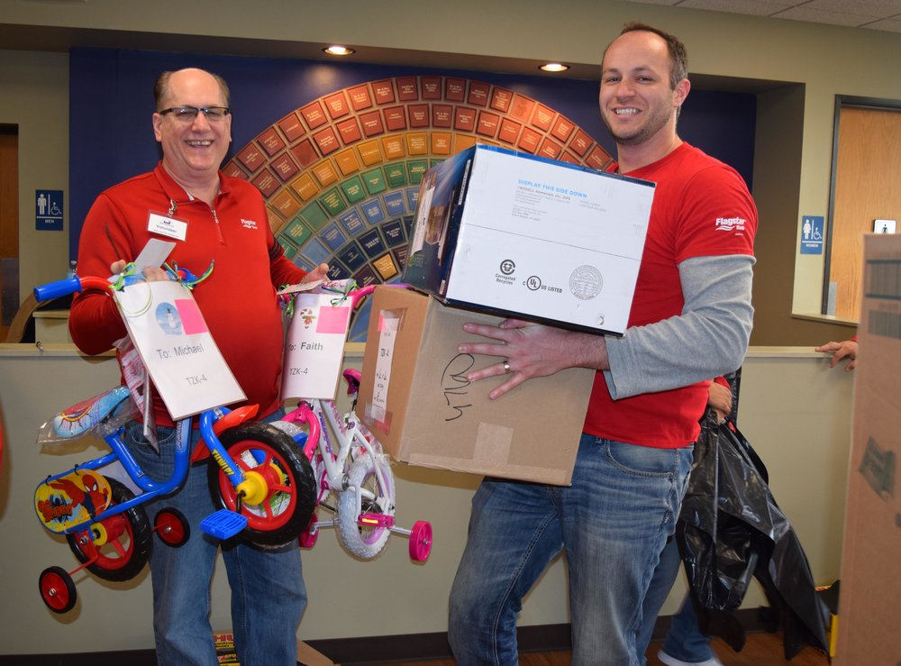 Volunteers carry gifts dropped off for Oakland Family Services' Adopt a Family program.