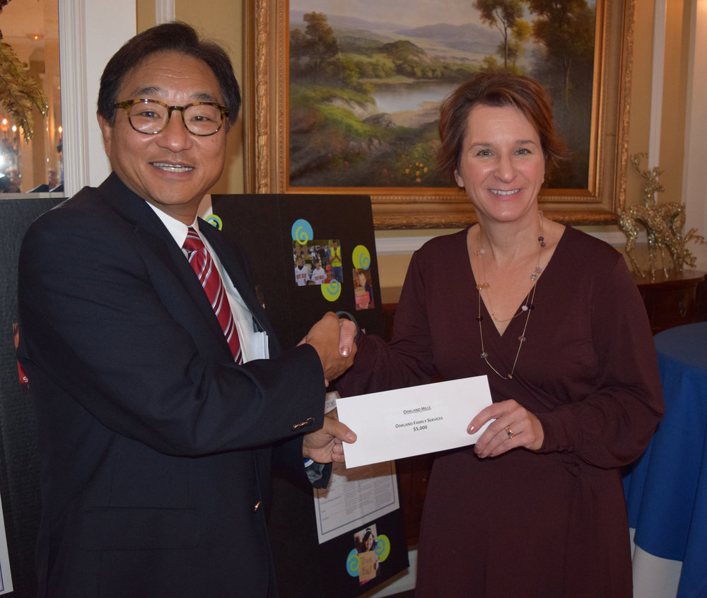 Hal Zaima, co-founder of Eagles for Children, presents Kris Kasperski, director of Early Childhood Services at Oakland Family Services, with funding for the Children's Learning Center in Pontiac.