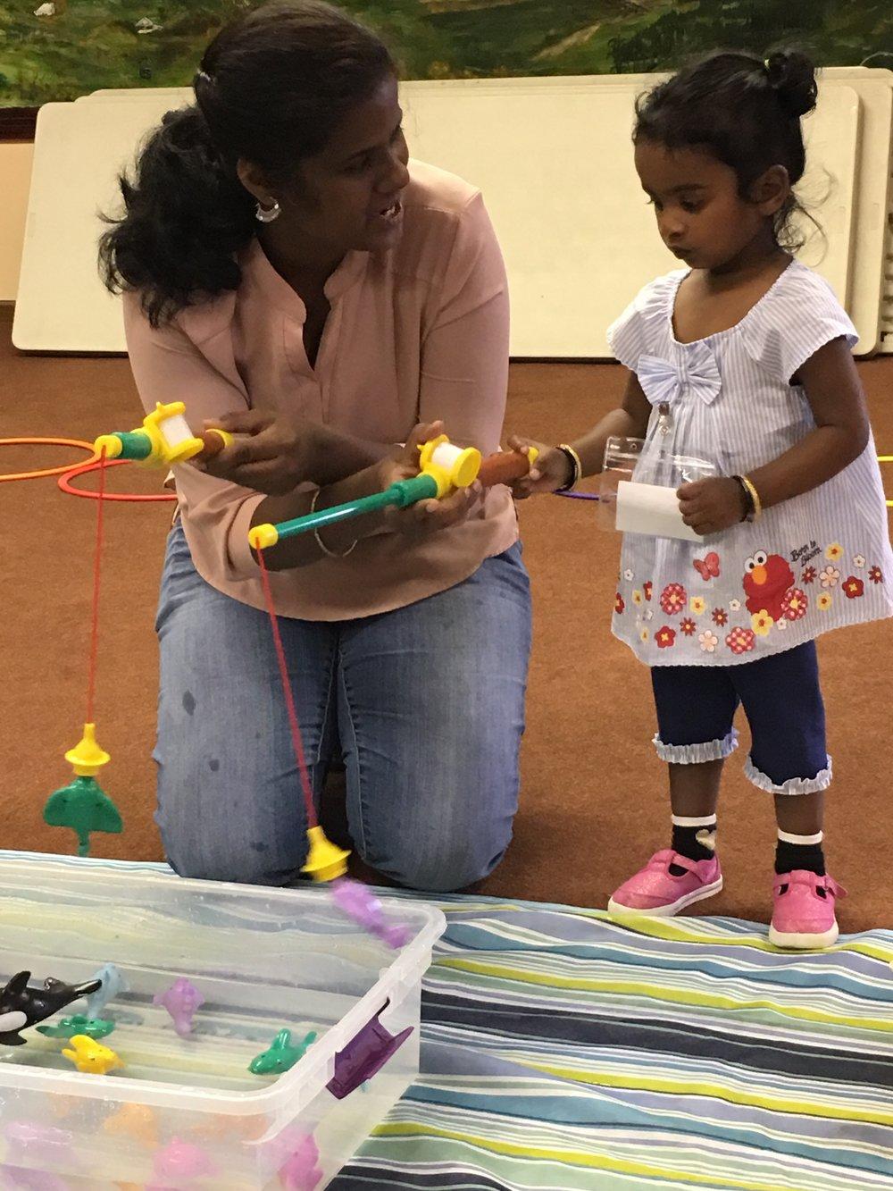Priya enjoys a fishing game with Advika at a playgroup.
