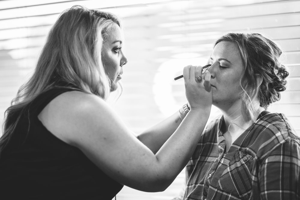 bride getting her makeup done on wedding day