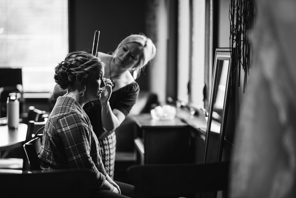 bride getting makeup done on her wedding day