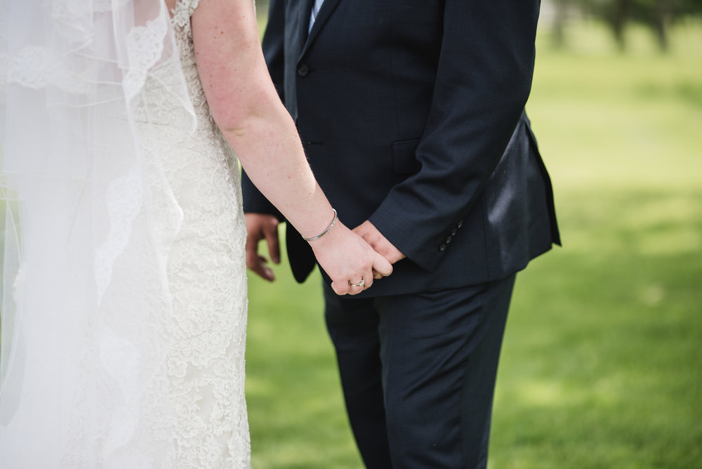 bride and groom hold hands at their first look