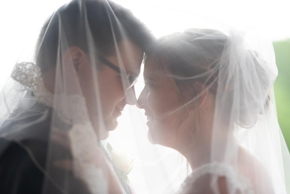 bride and groom under veil at wedding