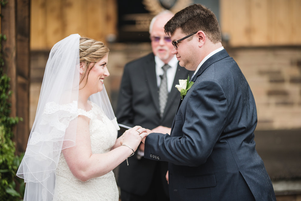 couple exchange rings at wedding trout club