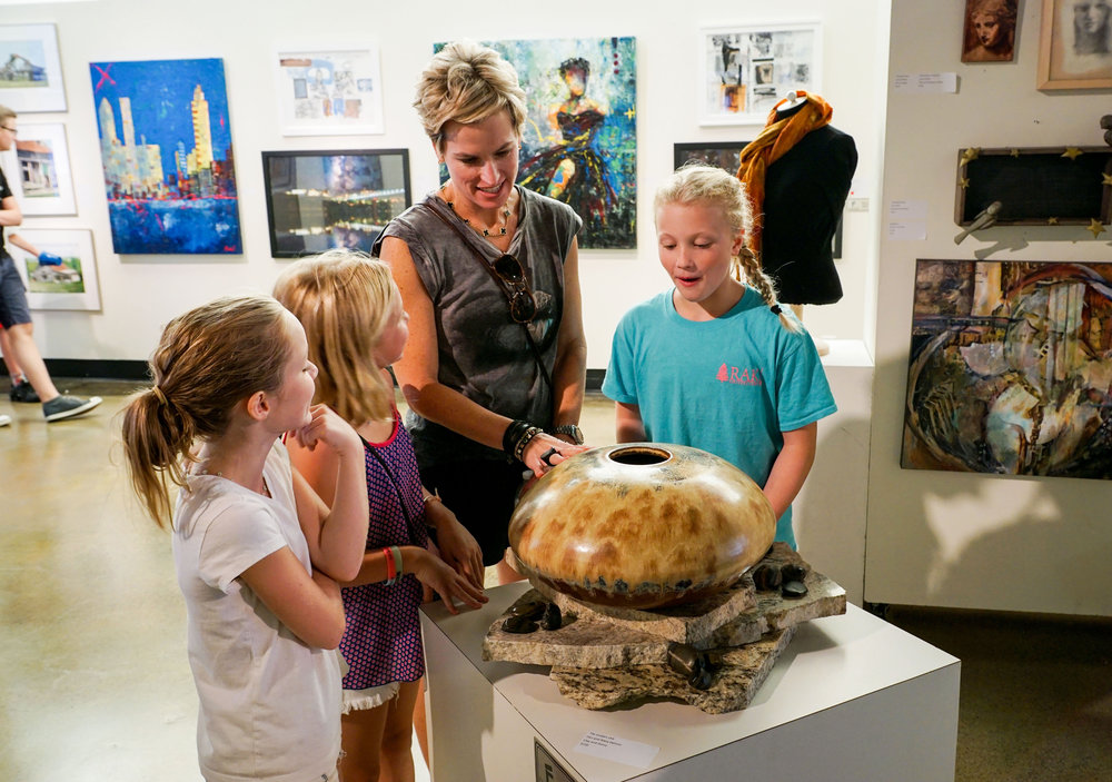 Jennifer Grafe and three young art collectors admire a decorative sculpture at the Creative Arts Guild's annual FESTIVAL.