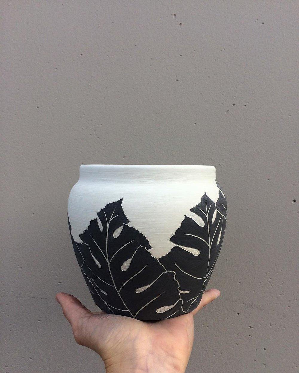 A decorative planter pot with an acanthus leaf design. Earthenware, slip, underglaze, sgraffito