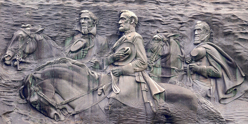 Robert E. Lee, Jefferson Davis and Stonewall Jackson are carved 400 feet above the ground on the side of Stone Mountain, in Georgia. The carving is protected by law, but Democratic candidate for governor, Stacey Abrams, called for the removal. (Wikimedia Commons)