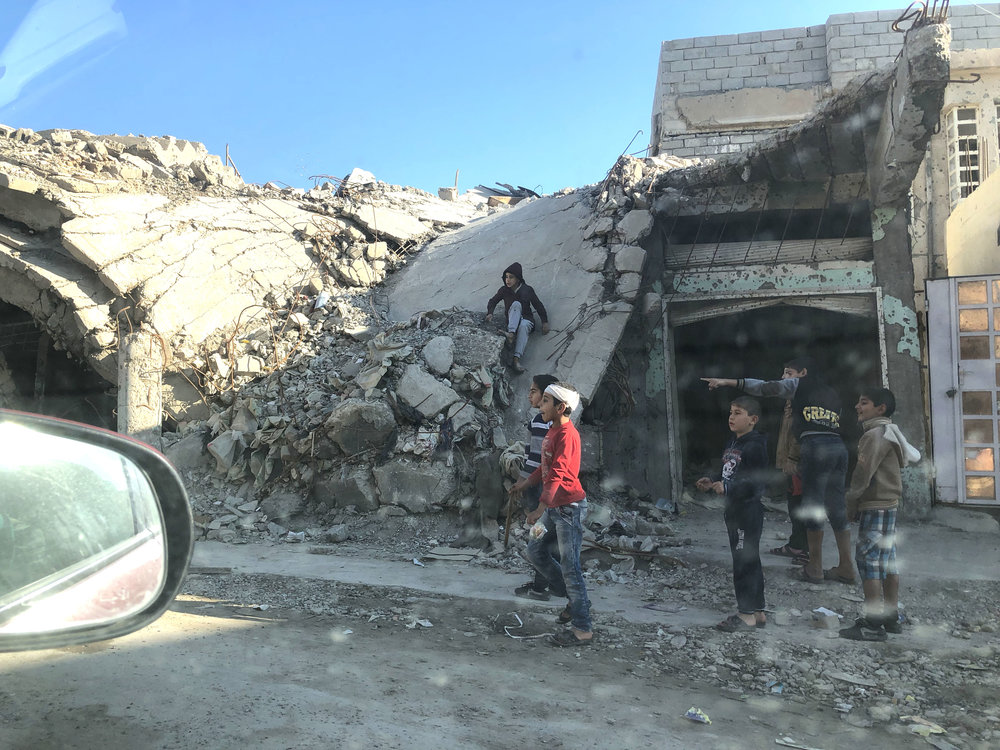 Children playing on rubble in western Mosul, as seen from the passenger seat of my translator's car. November, 2018. (Rebecca Gibian)
