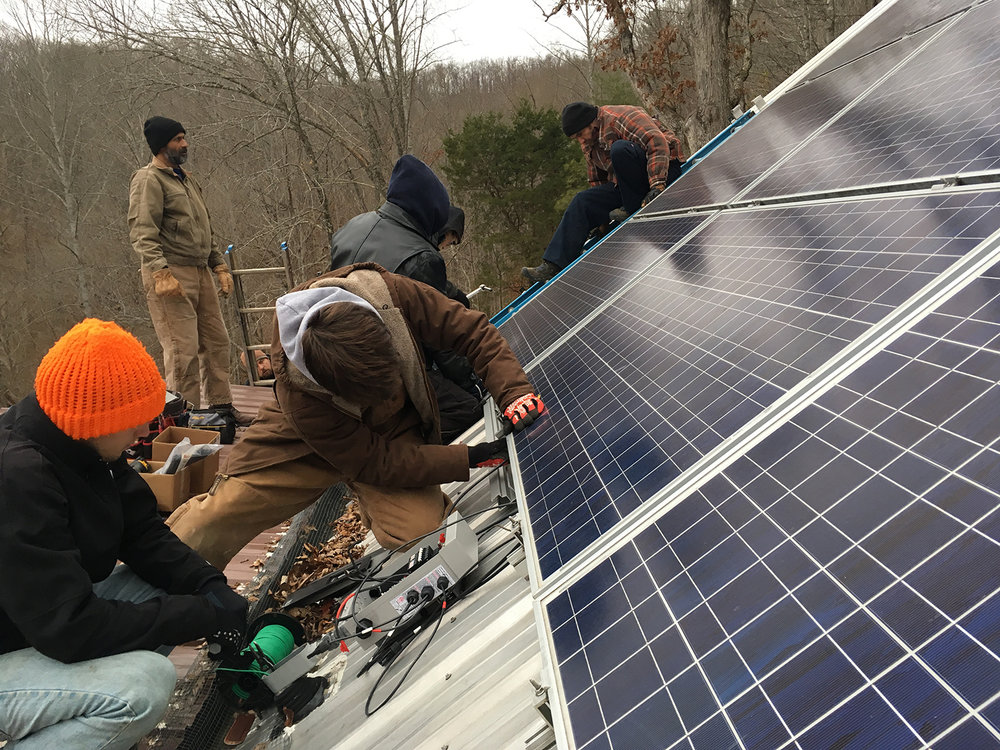 Workshop participants install additional panels and connect the wiring during the off-grid solar upgrade & expansion at Clear Creek in December 2016.  (photo by Carrie Brunk)