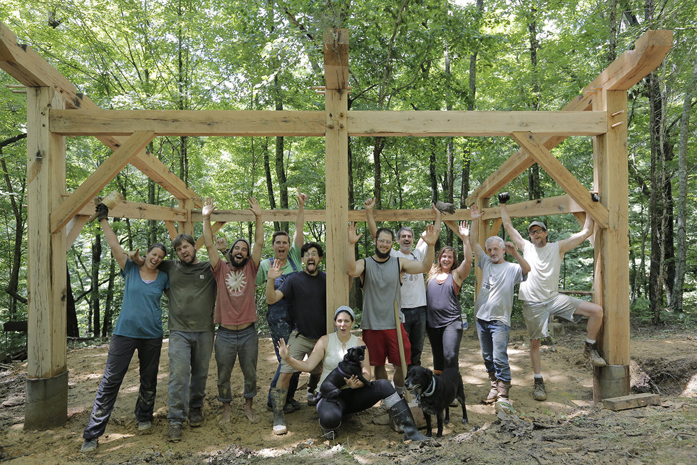 Carrie, Bob, Tyler, Nicole, Ziggy, April (with Pug), Jacob, Tim, Kayla, Jeff and Robert (and T-Bon in the lead) celebrate after raising the timberframe community kitchen.  (photo by Nick Slie)