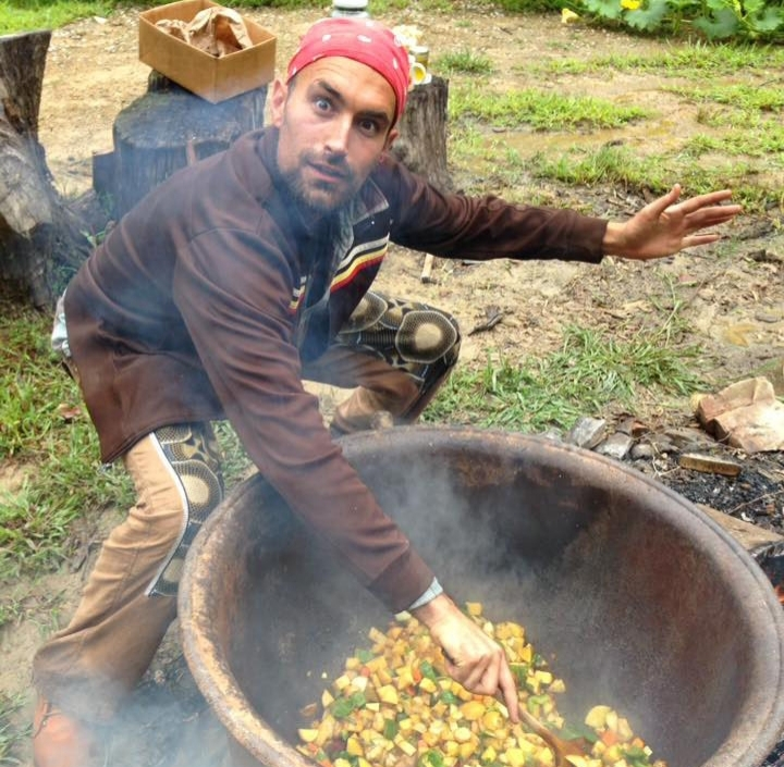 Joel Karabo Elliot cooks a stew with locally grown vegetables in a cast iron cauldron over an open fire in between bouts of rain from Hurricane Harvey. (photo by Nicole Garneau)