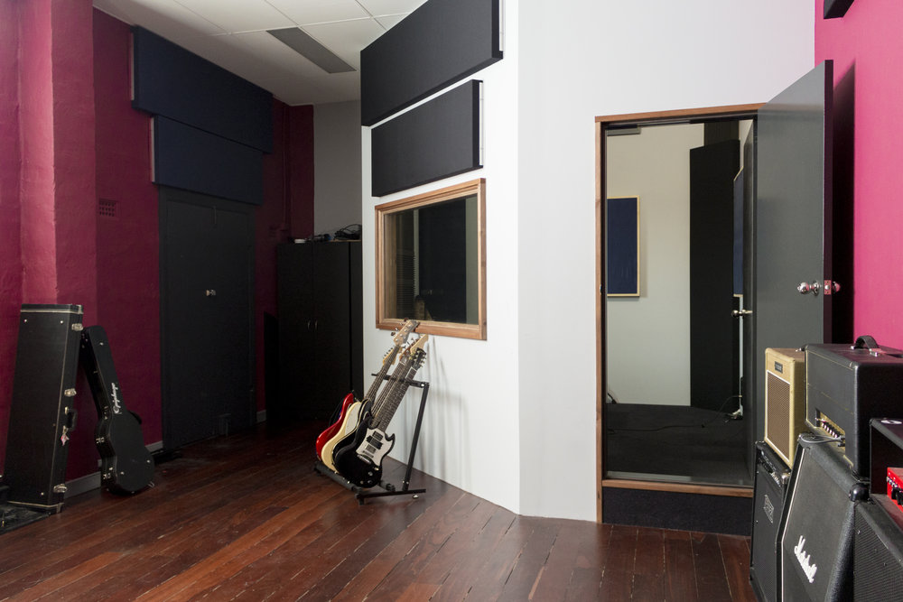 """Built to be our saving grace for live band tracking; the """"Isolation Booth"""" was carefully designed to ensure a great sound right off the bat for Drum, Bass, Guitar, and Horn instruments. It features a floating floor and ceiling, ideal bass control, naturally diffusive gem-shape, and tight sound with a touch of desired decay. This room is invaluable in live-tracking situations."""