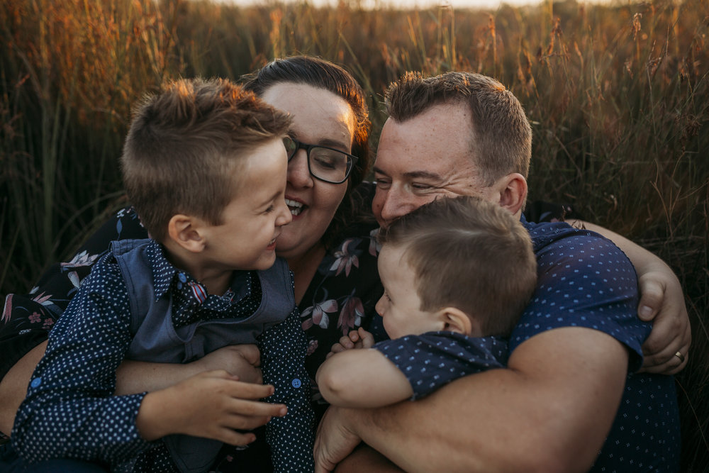 Mum and dad, with their two young boys sitting on their laps, wrapped in each others arms, hugging and laughing. They are sitting in a field of long bush grass with the golden sun setting behind them. Image by Jade Flores Photography