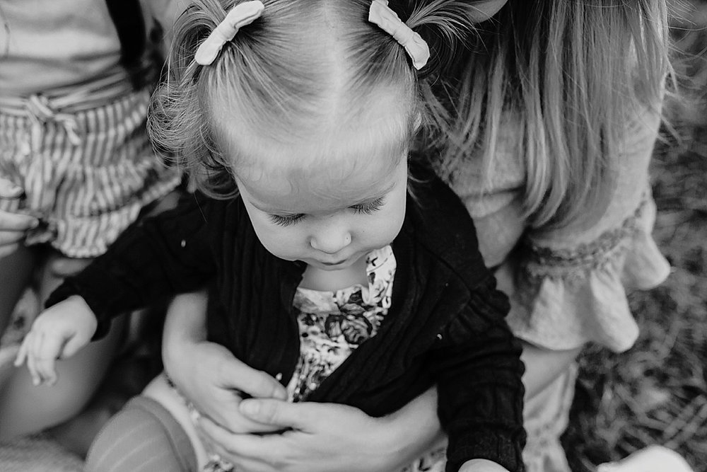Black and white image of little girl sitting down on mums lap